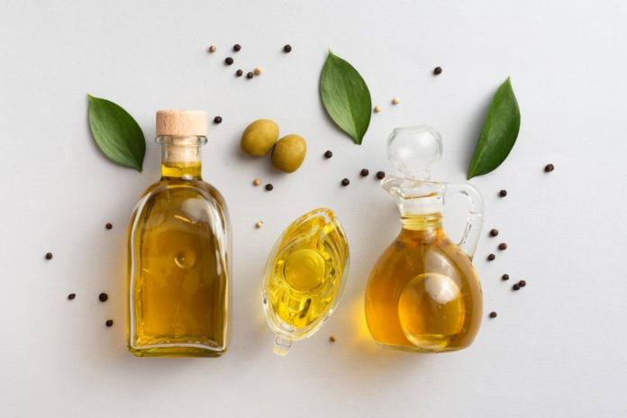 olive oils on tables with leaves and olives